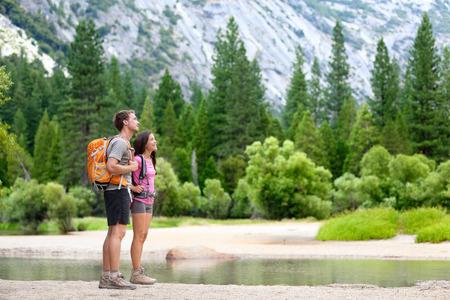 Wandelen mensen op trektocht in de bergen in Yosemite. Wandelaars jong stel wijzende op zoek naar in berglandschap in Yosemite National Park, California, USA. Multiculturele paar actieve buitenleven.