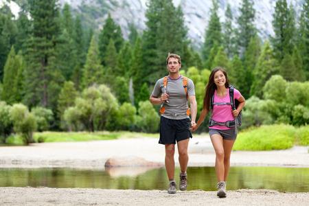 Wandern Personen auf Wanderung in den Bergen in Yosemite. Wanderer junges Paar zeigt auf der Suche nach oben in Berglandschaft im Yosemite National Park, Kalifornien, USA. Multikulturelle Paar draußen aktiv. Standard-Bild