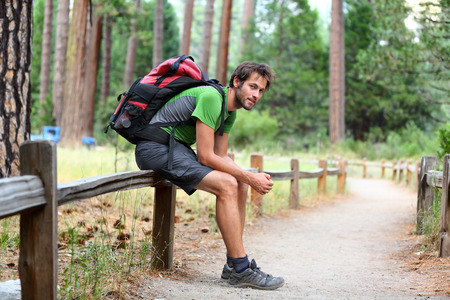 travel gear: Hiking man portrait with backpack tired resting legs after long hike in nature. Caucasian man smiling happy with forest in background during summer trip in Yosemite National Park, California, USA.