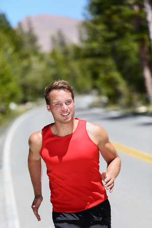Running runner training cardio on forest road. Male athlete working out jogging in nature on a summer day. Caucasian adult. photo
