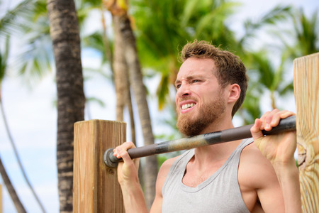 cross bar: Crossfit man working out pull-ups on chin-up bar. Portrait of bearded fit young man cross training arms on horizontal bars outside on outdoor gym in summer.