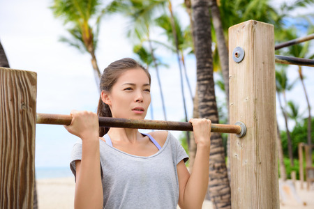 pullups: Fitness woman exercising on chin-up bar. Lady doing chin-ups training toned arms portrait outside on beach in summer. Stock Photo