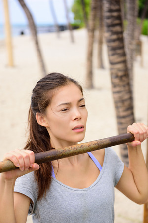 cross bar: Exercise woman training arms on pull-up bar doing chin-ups. Asian mixed race chinese caucasian female athlete working out on horizontal bars outside on beach.