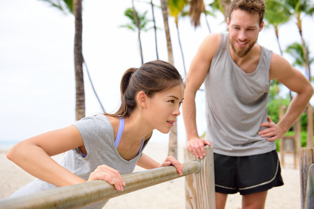 cross bar: Fitness instructor coaching and helping woman doing push-ups on cross fit horizontal bar station on beach. Arm press pushups easy exercises.