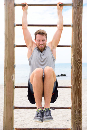 cross bar: Fitness people - man training abs by lifting legs on cross fit bar rack outside on outdoor gym station.