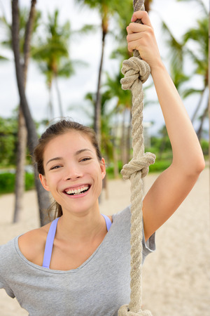 woman rope: Fitness girl portrait - healthy fit woman smiling. Adorable mixed race asian chinese female athlete holding crossfit climbing rope on outdoor beach gym outside. Stock Photo