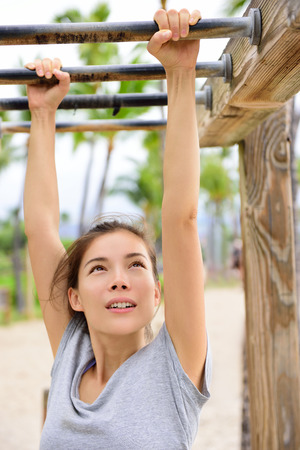 cross bar: Woman training on fitness brachiation ladder or monkey bars hanging swinging from rung to rung as part of crossfit workout routine. Beautiful Asian girl doing toning exercises exercising arms.