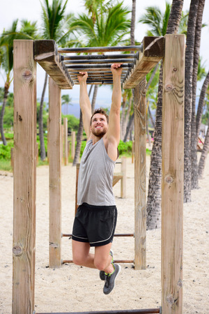 hang body: Fitness man on monkey bars fitness station gym. Strong male trainer training on brachiation ladder outdoors equipment as part of crossfit workout routine.