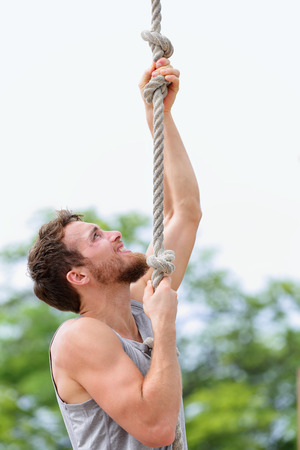 Crossfit man doing rope climb workout outside during summer. Handsome male athlete climbing up rope for strength training session. photo