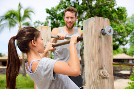 Fitness couple training on chin-up bar together. Woman helped by friend or private instructor on coaching session supervising exercises on outdoor beach gym.