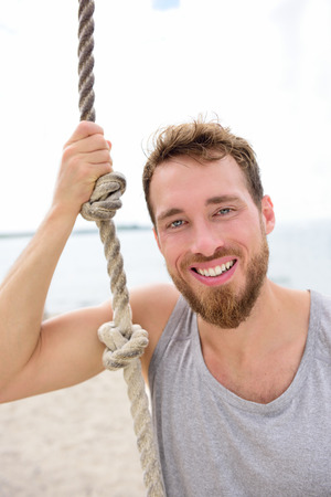 Fitness people portrait - healthy man with rope. Happy adult on summer beach showing climbing rope used in crossfit workout for strength training. photo