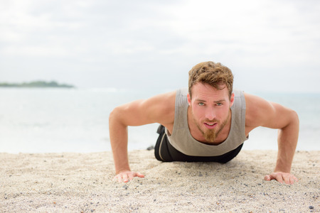 man working out: Push-ups - crossfit man fitness model training pushups on beach outdoors. Fit male fitness trainer working out exercising in summer on beach.