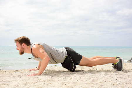 pushup: Push-ups - man fitness model training pushups on beach outdoors. Fit male fitness trainer working out exercising in summer on beach. Stock Photo