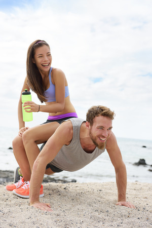 Fitness couple training doing funny push-up on beach during workout. Woman playful having fun sitting on boyfriend to test his strength with heavy weight.