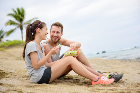 fit women: Salad - healthy fitness woman and man couple laughing eating food lunch sitting on beach after workout. Mixed race Asian Caucasian female model and male models in sportswear.
