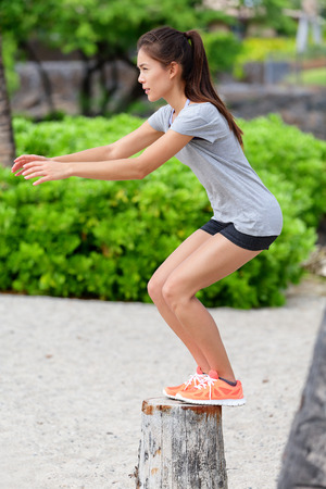 girl working out: Fitness woman athlete bench jump squat jumping outside in nature landscape. Strength training fit girl working out exercising outdoors on beach in summer doing jumping on tree trunk. Stock Photo