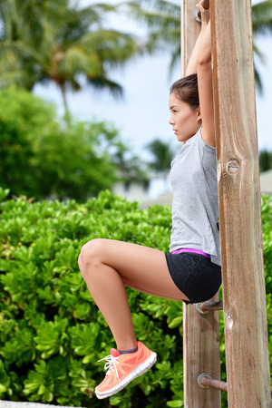vertical bars: Fitness woman workout doing abs exercises on outdoor beach gym. Asian girl training abs by raising legs on a vertical bars rack during a fitness station circuit routine. Stock Photo