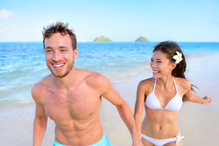 bikini island: Happy couple having fun on beach vacation during summer holiday. Multiracial fit couple running together holding hands laughing in the sun. Young adults in shape carefree feeling good in their body. Stock Photo