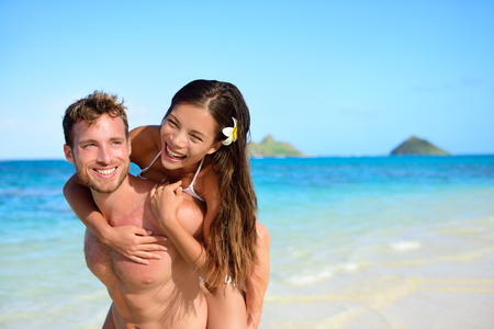 mixed race couple: Beach couple vacation fun - happy piggyback. Cute mixed race asian chinese woman piggybacking on the back of handsome caucasian man laughing in love during summer holidays or vacations in Hawaii, USA.
