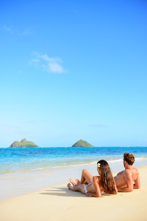 Beach vacations suntan couple relaxing in Lanikai, Oahu, Hawaii, USA. Vertical crop with blue sky copy space background for holiday vacation travel concept. photo