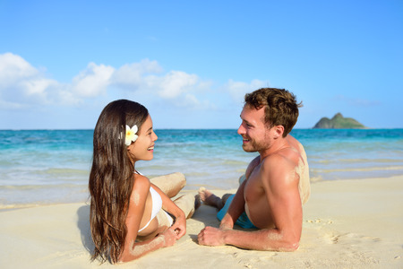 Couple in love relaxing on beach during vacation travel. Happy couple portrait talking together in a happy relationship sun tanning lying on the sand having fun in Hawaii, United States of America. photo