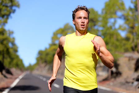 Running man sprinting for success on run. Male athlete runner training at fast speed. Muscular fit sport model sprinter exercising sprint on forest road. Caucasian fitness model in his 20s.