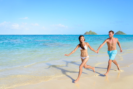 Beach vacations - happy couple running together joyful in water during holidays in Hawaii. photo