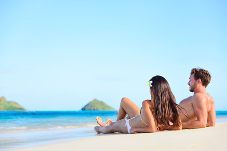 Beach sun tan couple relaxing on holiday in Hawaii. Vacations holidays suntan concept - adults lying down tanning on luxury exclusive beach in Lanikai, Oahu, Hawaii, USA. photo