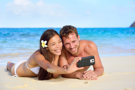 Beach holiday couple taking selfie with smartphone lying down relaxing and having fun holding smart phone camera. Young beautiful multicultural Asian Caucasian couple having fun on summer beach. photo