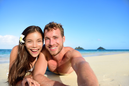 Couple relaxing on beach taking selfie picture with camera smartphone. Young multiracial couple on getaway vacation in Hawaii lying down looking at camera. Candid closeup angle looking real. photo
