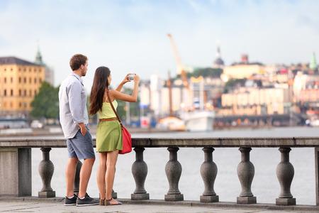 Châu Âu đi du lịch người chụp ảnh. Khách du lịch trong vài Stockholm chụp ảnh điện thoại thông minh có vui vẻ thưởng thức nhìn đường chân trời và dòng sông bởi Tòa thị chính Stockholm, Thụy Điển. Kho ảnh