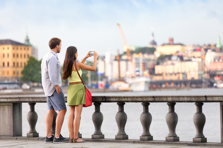 traveller: Europe travel tourist people taking pictures. Tourists couple in Stockholm taking smartphone photos having fun enjoying skyline view and river by Stockholms City Hall, Sweden. Stock Photo