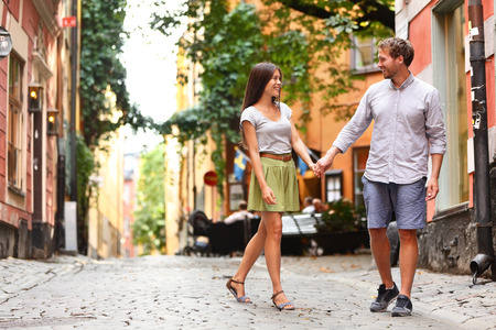 city: Happy couple in love walking in Gamla Stan, Stockholm city visiting Sweden. Young adults tourists on travel or Swedish urban people in summer walking on a date. Stock Photo