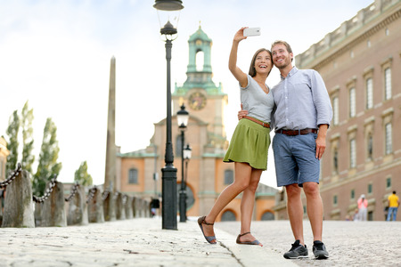 Selfie couple taking pictures in the capital of Sweden. Tourists people taking travel photos with smartphone on summer holidays.