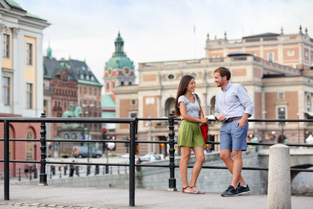 Urban people street lifestyle - couple of tourists on travel or smart casual modern young professionals talking in Stockholm city, Sweden. Foto de archivo