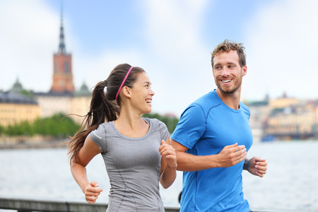 buddies: Healthy runners running in Stockholm city cityscape background. Riddarholmskyrkan church in the background, Sweden, Europe. Healthy multiracial young adults, asian woman, caucasian man. Stock Photo