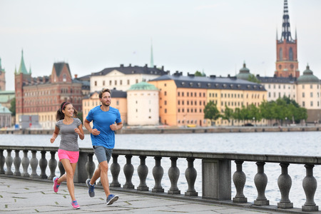 girl in sportswear: Fit fitness exercise people, healthy runners running in Stockholm city cityscape skyline. Riddarholmskyrkan church in the background, Sweden, Europe. Healthy multiracial young adults, asian woman, caucasian man. Stock Photo