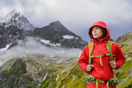 life jackets: Alps Hiking - Asian hiker woman in Switzerland on trek in mountains with backpack living a healthy active lifestyle. Hiker girl on nature landscape hike in Urner Alps, Berne, Swiss alps, Switzerland.