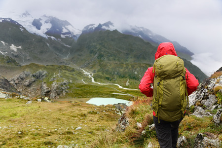 rain coat: Hiking - hiker woman on trek with backpack living healthy active lifestyle. Hiker girl walking on hike in mountain nature landscape in Steingletscher, Urner Alps, Berne, Swiss alps, Switzerland.