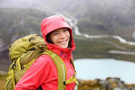 ハイカー女性は健康的な生活のトレッキングに雨の中でバックパックをハイキングします。新鮮なと率直なアジアの少女スイス スイス アルプスで雨 写真素材