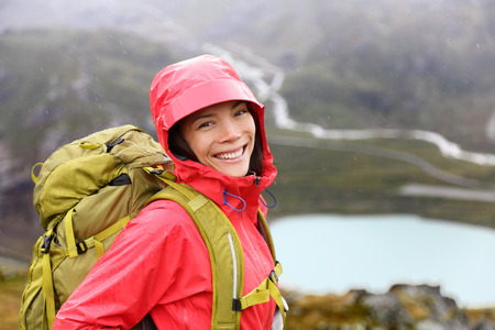 Hiker woman hiking with backpack in rain on trek living healthy life. Smiling fresh and candid young asian girl walking on hike in mountain nature landscape while raining in Swiss alps, Switzerland. photo