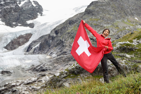 Switzerland hiker hiking cheering showing Swiss flag jumping in front of glacier. Happy Asian woman holding big red flag in nature. photo