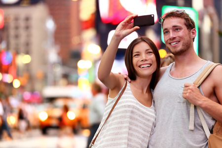 tourism: Travel tourist couple taking selfie with smartphone in New York City, USA. Self-portrait photo on Times Square at night. Beautiful young tourists having fun, Manhattan, USA. Asian woman, Caucasian man