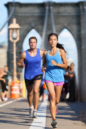 New York runners running training on Brooklyn bridge NYC during busy rush hours with tourists. Fit young couple doing their workout routine on a summer day. photo
