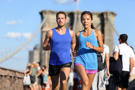 City running couple jogging outside. Runners training outdoors working out in Brooklyn with Manhattan, New York City in the background. Fit multiracial fitness couple, Asian woman, Caucasian man. Stock Photo