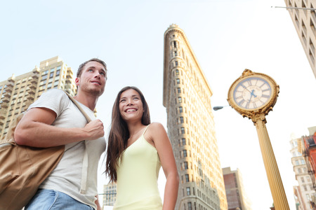 NYC tourism - tourists visiting New York city standing in front of Flatiron building. Young couple of tourists in New York City looking at famous landmark buildings during summer.