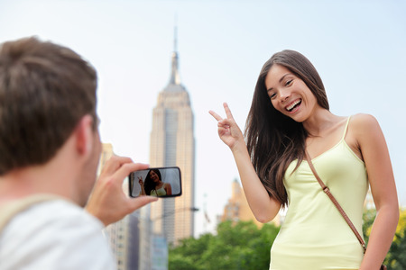 NYC asian chinese tourist girl posing at Empire State Building doing the v hand sign. Young couple of tourists taking pictures with smartphone in New York City in front of famous landmark building. photo