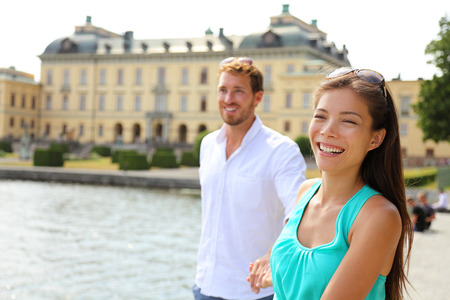 Stockholm couple at Drottningholm palace, Sweden. Tourist people visiting the Queens royale residence in Stockholm, famous attraction in Sweden. Asian caucasian couple in Europe Scandinavia. photo