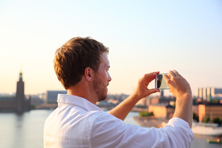 Tourist taking photograph of sunset in Stockholm skyline and Gamla Stan. Man photographer taking photos using smartphone camera. Male traveler sightseeing visiting landmarks in Sweden, Scandinavia. Banque d'images