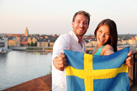 sweden flag: Swedish people holding Sweden flag in Stockholm. Candid fresh Scandinavian man and Asian woman looking at old town cityscape sunset view from Monteliusvagen overlooking Gamla Stan, the old city.